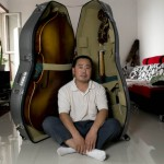 Luthier Mr Gao ZhenMin in front of his folded double-bass inside the case.