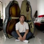 Mr Gao ZhenMin devant une contrebasse pliée dans sa caisse.
