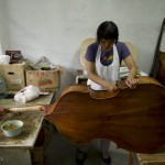 Ms Wen YaXia varnishing an instrument in the couple's workshop.