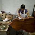 Mme Wen YaXia vernit une contrebasse dans son atelier du Hebei.