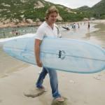 Adam Healy l'un des deux propriétaires de Benpat International avec une planche de surf Ark sur la plage de Shek-O sur l'île de Hong Kong.