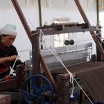 4.一位当地妇女在工作室里的木纺织机上制作批巾