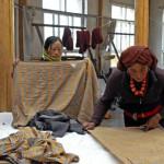 Deux femmes travaillent sur deux châles aux motifs différents faits pour une grande maison de couture parisienne.