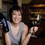 Judy Leissner, Grace Vineyard CEO with a bottle and a glass of Deep Blue, the flagship wine in the tasting wine cellar.