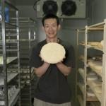 刘阳在发酵室里展示一块Tomme奶酪