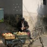 三轮车的另一个用处:在北京钟楼附近胡同里卖水果的小贩 (Lionel Derimais摄)
