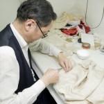 Lau 先生正在制作一件带衬里的旗袍,它必须先用胶水粘上然后再缝在一起。
