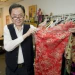 Lau 先生正在展示他的最新作品:一件用丝绸和产自法国加莱的蕾丝制成的旗袍。