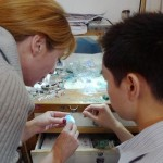Paloma Sanchez examines a Sleeping Beauty turquoise from Arizona with one of the goldsmith who works in her workshop in Beijing.