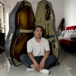 Gao Zenmin the bass maker in his home in Hebei with a folding double-bass and its case.