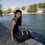 """Michelle Lai à Paris, sur l'Ile de la Cité, dans de parc du Vert-Galant au bord de la Seine avec l'une de ses créations: le sac """"Overnighter"""" de la collection Mischa """"Travel""""."""