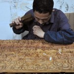 One of Mr Kele Ma's carpenter carving the door of a scented rosewood cabinet with dragon patterns. This type of cabinet was popular during the Qing Dynasty.