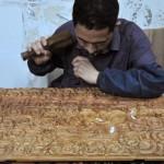 工坊中的一位雕刻师傅在制作黄梨木质地,带有龙纹的门板。这一图案在清朝非常盛行