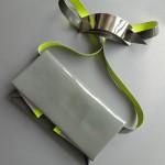 Le sac à main Agenda par Katrin Reinfurt / MPMP. Fait de cuir de chèvre ce sac est gris avec une finition vernie très brillante. Ce sac à main est fait d'une seule pièce pliée sans couture ni colle.